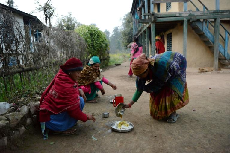 Nepalese women Pabitra Giri (L) and Yum Kumari Giri prepare to have dinner outside their house during their menstruation period, in Surkhet District, some 520 km west of Kathmandu
