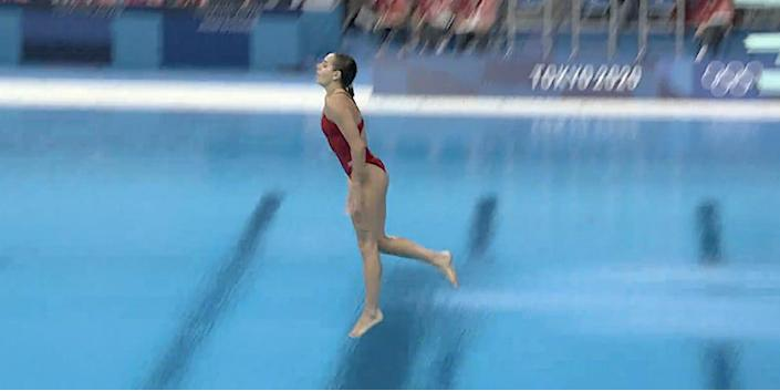 Screenshot shows Pamela Ware going feet first into the pool on a dive attempt at the Tokyo Olympics.