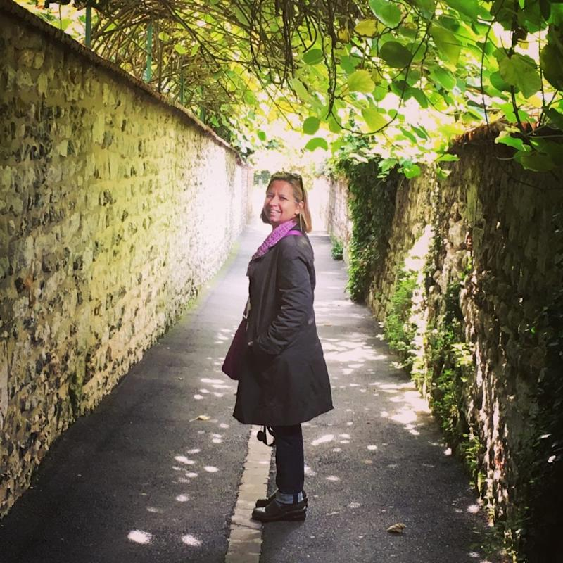 woman standing in an outdoor corridor with stone walls and a ceiling covered with leaves