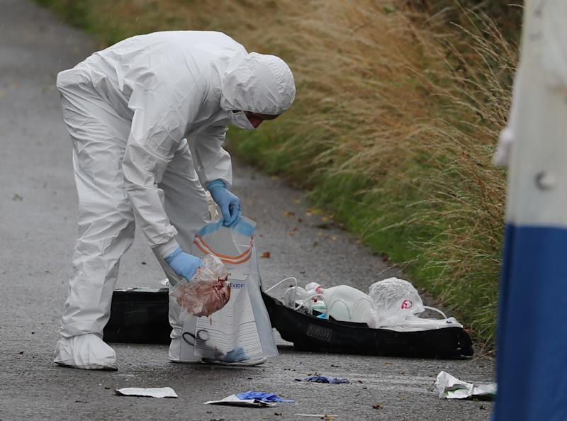 A police investigator places items in a bag at the scene of an incident, near Sulhamstead, Berkshire, where a Thames Valley Police officer was killed whilst attending a reported burglary on Thursday evening.