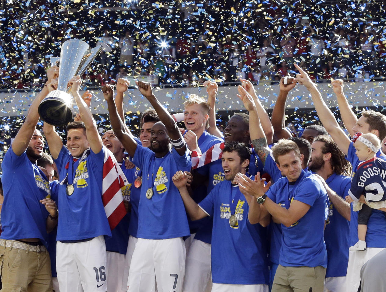 United States' Jose Torres (16), left, holds the trophy as he celebrates with teammates after defeating Panama 1-0 during the CONCACAF Gold Cup final soccer match at Soldier Field, Sunday, July 28, 2013, in Chicago. (AP Photo/Nam Y. Huh)
