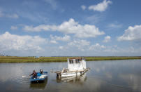 Nicholas Bartholomew, 78, who has been a shrimper since he was 15-years-old, paddles out to check on his boat that floated away from its mooring on Grand Bayou near Highway 23 in Plaquemines Parish over a week after Hurricane Ida on Tuesday, Sept. 7, 2021. (Chris Granger/The Times-Picayune/The New Orleans Advocate via AP)