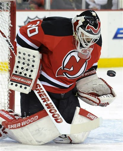 New Jersey Devils goaltender Martin Brodeur reaches to glove the puck during the first period of an NHL hockey game against the Anaheim Ducks on Friday, Feb. 17, 2012, in Newark, N.J. (AP Photo/Bill Kostroun)
