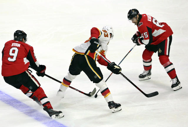 Ottawa Senators defenseman Erik Karlsson (65) and right wing Bobby Ryan (9) attempt to check Calgary Flames center Sam Bennett (93) during the first period of an NHL hockey game in Ottawa, Friday, March 9 2018. (Fred Chartrand/The Canadian Press via AP)