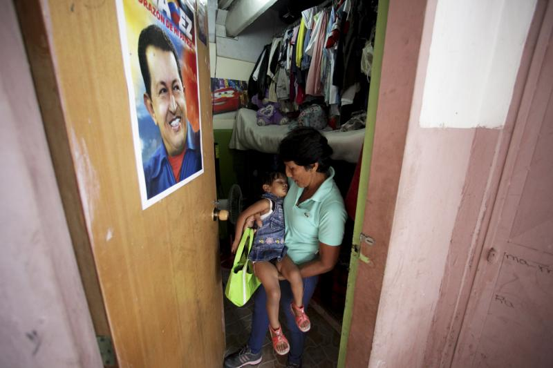 In this Sept. 27, 2012 photo, a poster of Venezuela's President Hugo Chavez hangs on the door where Maria Perez carries her granddaughter out of the room where they live that was once a school room and is now part of a government provided shelter for families who lost their homes due to flooding, in Caracas, Venezuela.  Fear of every stripe, like the loss of government housing like this one, permeates the intensely polarized election campaign, with many votes to be decided based not on the candidates' promises but rather on what worries people most. Chavez has continuously warning of chaos and the dismantling of the generous welfare state he built if he is voted out of office in the Oct. 7 vote. (AP Photo/Fernando Llano)