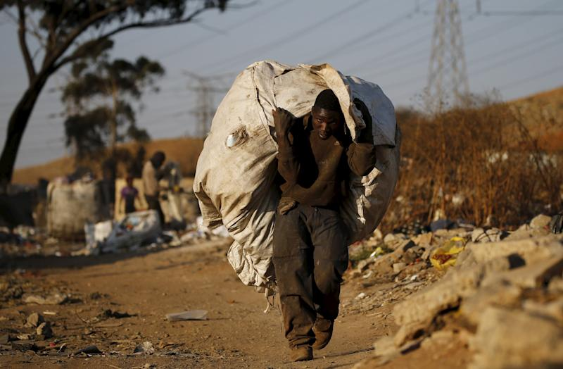An unemployed man carries a bag full of recyclable waste material which he sells for a living, in Daveland near Soweto