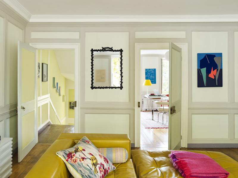 The large living room opens onto the couple's study. The mirror is one of several around the house by Marianna Kennedy; many of the lamps are hers as well. Irwin had the B&B Italia modular sofa custom-upholstered in a vibrant mustard yellow.