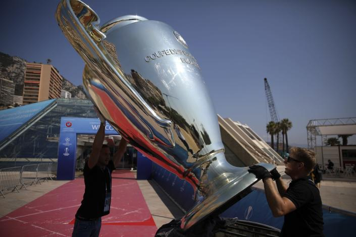 Workers install a giant replica of the Champions League trophy ahead of the UEFA group stage draw outside the Grimaldi Forum, in Monaco, Thursday, Aug. 29, 2019. (AP Photo/Daniel Cole)