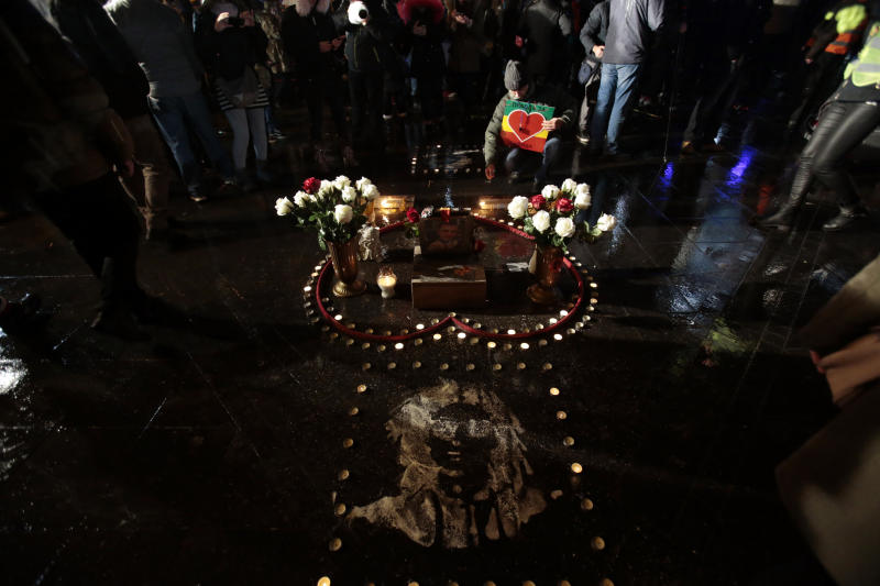 A man lights candles during a protest, in Banja Luka, Bosnia on Sunday, Dec. 30, 2018. Several thousand Bosnians have rallied in support of the man whose quest for the truth about his son's death has turned into a wider movement for justice and rule of law in the Balkan country. The protest on Sunday demanded the ouster of Bosnian Serb Interior Minister Dragan Lukac and top police officials over the death in March of 21-year-old David Dragicevic. (AP Photo/Amel Emric)
