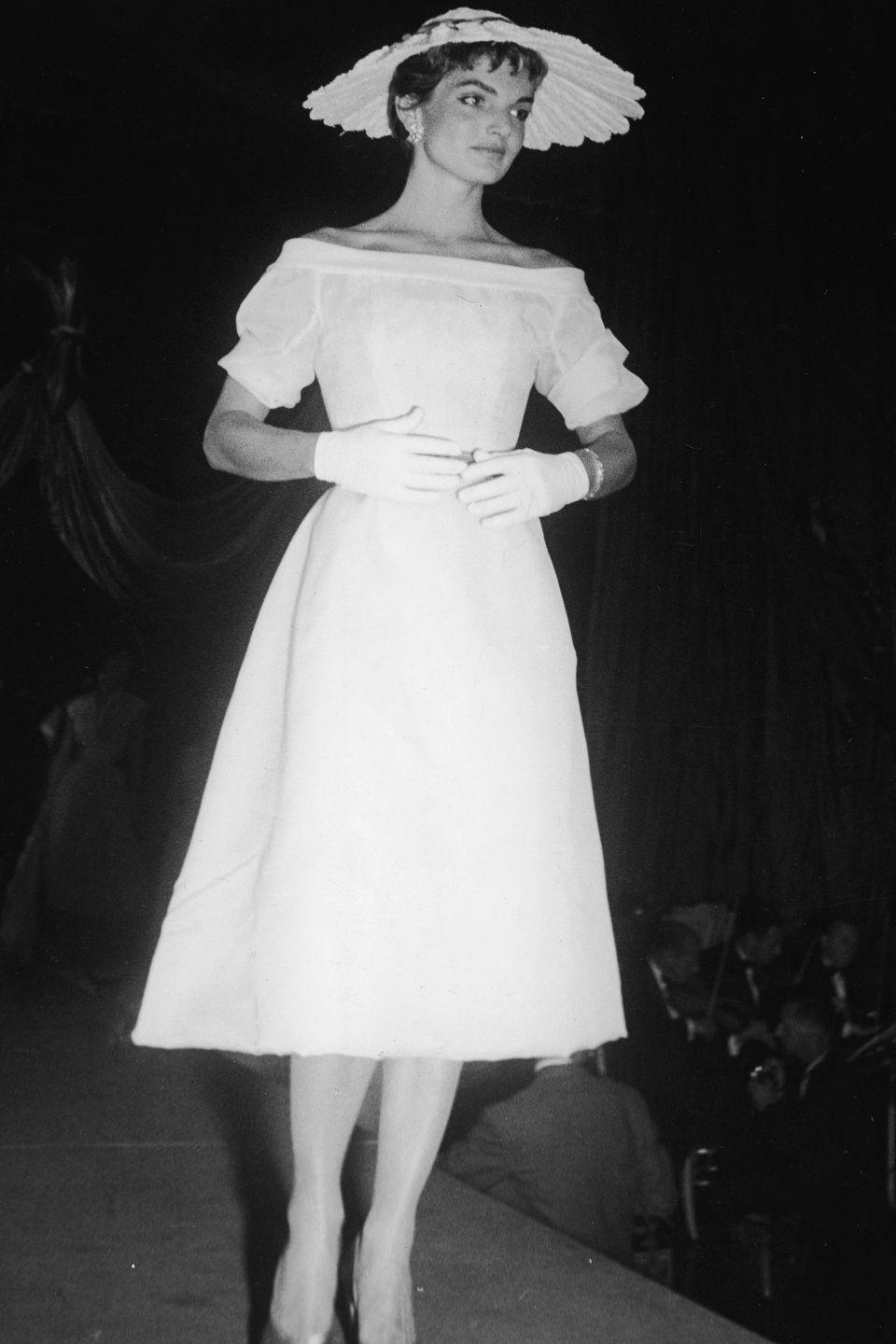 <p>All-white was a theme for Mrs. Kennedy, shown here in a white hat and another boat neck. Those white gloves finish the elegant look.</p>