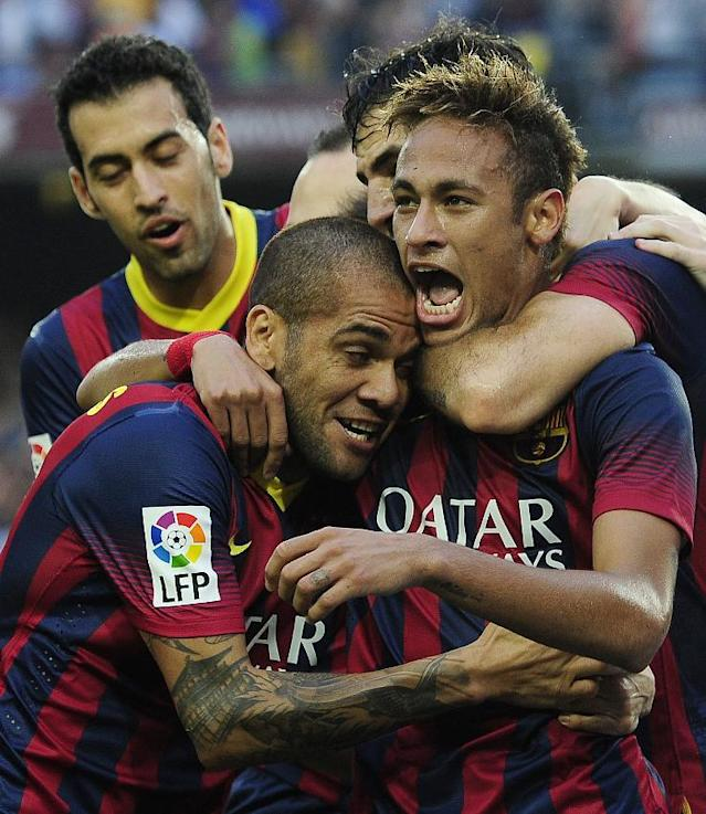 FC Barcelona's Neymar, right, from Brazil, celebrates scoring against Real Madrid with teammates Daniel Alves, from Brazil, second left, and Sergio Busquets, left, during a Spanish La Liga soccer match at the Camp Nou stadium in Barcelona, Spain, Saturday, Oct. 26, 2013. (AP Photo/Manu Fernandez)