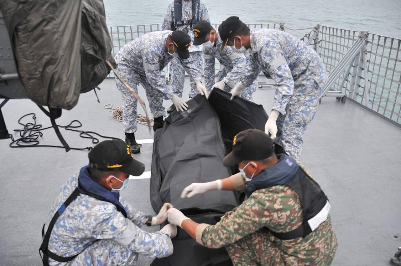 <p>In this photo released by the Royal Malaysian Navy, navy sailors cover an unidentified body on to the deck of KD Lekiu frigate after it was recovered in the waters off the Johor coast of Malaysia, Aug. 22, 2017. (Photo: Royal Malaysian Navy via AP) </p>