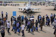 Foreign military officers and other visitors walk past the J-10C fighter jet from the Chinese People's Liberation Army (PLA) Air Force on display during the 13th China International Aviation and Aerospace Exhibition, also known as Airshow China 2021, on Tuesday, Sept. 28, 2021, in Zhuhai in southern China's Guangdong province. (AP Photo/Ng Han Guan)