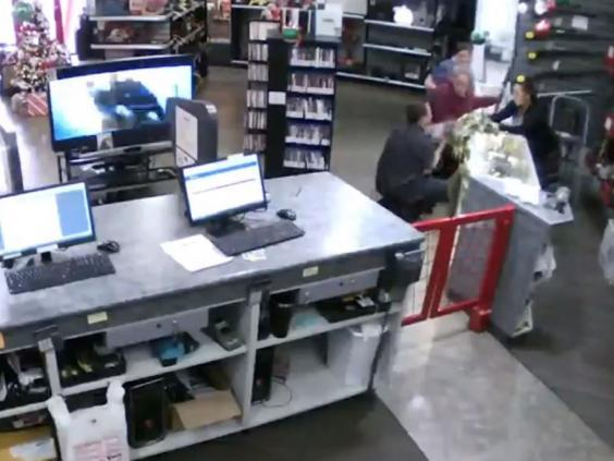 Still image from CCTV footage shows store manager Bill Reel catching a baby as it falls off a shop counter while two women look at a gun in Family Pawn in Utah, US. (Bill Reel)