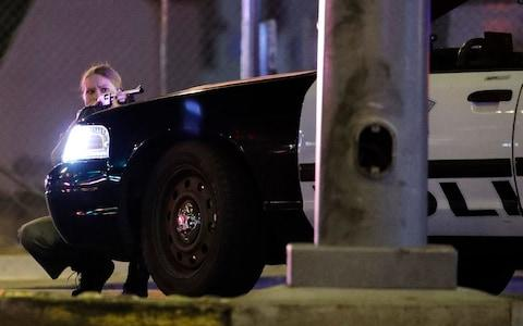 A police officer takes cover behind a police vehicle during a shooting near the Mandalay Bay  - Credit: John Locher/AP