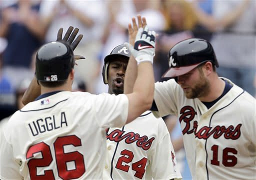 Atlanta Braves' Dan Uggla (26) gets a high-five from teammates Michael Bourn (24) and Brian McCann (16) after hitting a three-run home run in the third inning of a baseball game against the Toronto Blue Jays, Saturday, June 9, 2012, in Atlanta. (AP Photo/David Goldman)