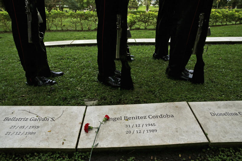 Police stand next to the graves of people who died during the 1989 U.S. military invasion that ousted Panama's strongman Manuel Noriega, on the 30th anniversary of the invasion, during a ceremony in honor of the dead at Jardin de Paz cemetery in Panama City, Friday, Dec. 20, 2019. According to official figures, 300 Panamanian soldiers and 214 civilians died during the invasion, though the number remains controversial and human rights groups believe it is much higher. Twenty-three U.S. soldiers also perished. (AP Photo/Arnulfo Franco)