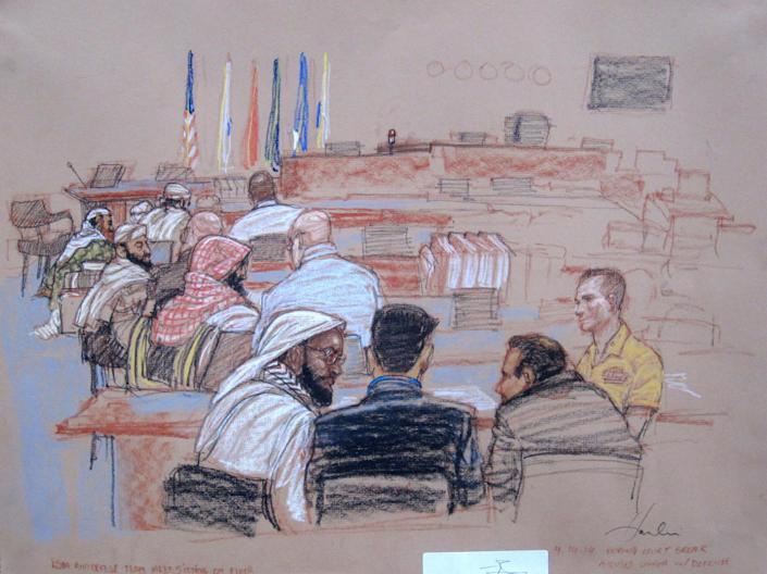 In this pool photo of a Pentagon-approved sketch by court artist Janet Hamlin, defendants speak with their defense lawyers during a break in pretrial hearings at the Guantanamo Bay U.S. Naval Base in Cuba, Monday, April 14, 2014. From right to left are Mustafa al Hawsawi, Ali Abdul Aziz Ali, Ramzi bin al Shibh, and Khalid Sheikh Mohammad sitting on the floor with Walid bin Attash sitting on a chair. A lawyer for one of five defendants in the Sept. 11 war crimes tribunal said Monday that FBI agents questioned a member of his defense team, apparently in an investigation related to the handling of evidence, a revelation that brought an abrupt halt to proceedings. (AP Photo/Janet Hamlin, Pool)