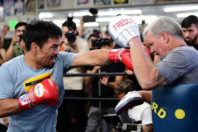 Manny Pacquiao (L) spars with trainer Freddie Roach in Hollywood ahead of Saturday's clash with Keith Thurman (AFP Photo/FREDERIC J. BROWN)