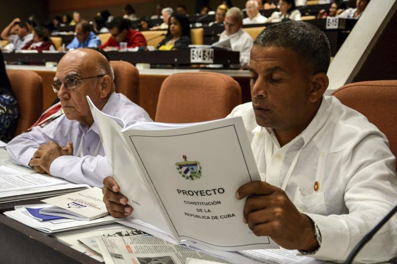 A member of the National Assembly studies the proposed update to the Constitution, in Havana, Cuba, Saturday, July 21, 2018. Cuban lawmakers approved the Cabinet named by new President Miguel Diaz-Canel, keeping most of the ministers from Raul Castro's government in place. (Abel Padron, Agencia Cubana de Noticias via AP)