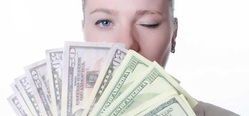 Young woman holding lots of cash and winking.