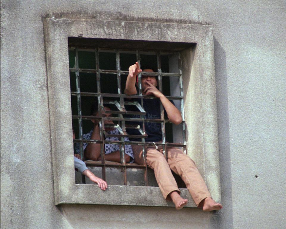 Inmates of the Carinduru prison shout from a window during a rebellion in Sao Paulo, Monday, May 5, 1997. A dozen prisoners seized twelve guards as hostages in an attempet to call attention to the over-population in the prision and asked to be transferred to a less-crowded facility. After a few hours of negotiation, police agreed to transfer the rebels to a different prison and the hostages were freed. (AP Photo/Robson Martins)