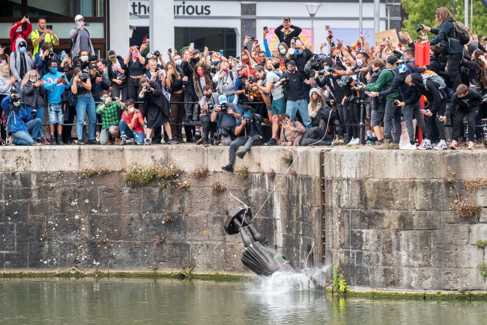 A statue of 17th-century slave trader Edward Colston falls into the water in Bristol, England, on June 7 after protesters pulled it down during a protest against racial inequality. (Keir Gravil via Reuters)