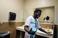 """Jerry Simmons, 49, holds a cup just before he takes a drug test in a restroom in St. Louis on Thursday, May 20, 2021. """"I just want to be a normal person back in society, working, living, loving, playing with my grandkids, making my kids be proud of me,"""" said Simmons, who's been addicted for 30 years, homeless and in and out of prisons. (AP Photo/Brynn Anderson)"""