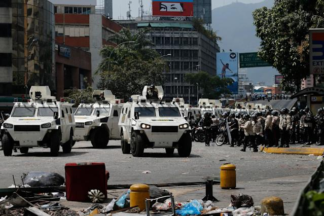 Bolivarian National Guard armored vehicles arrive during clashes between anti-government protesters and motorcyclists in the Los Ruices neighborhood of Caracas, Venezuela, Thursday, March 6, 2014. Venezuelan officials say a National Guard member and a civilian were killed in the clash between residents and armed men who tried to remove a barricade placed by anti-government protesters. (AP Photo/Fernando Llano)