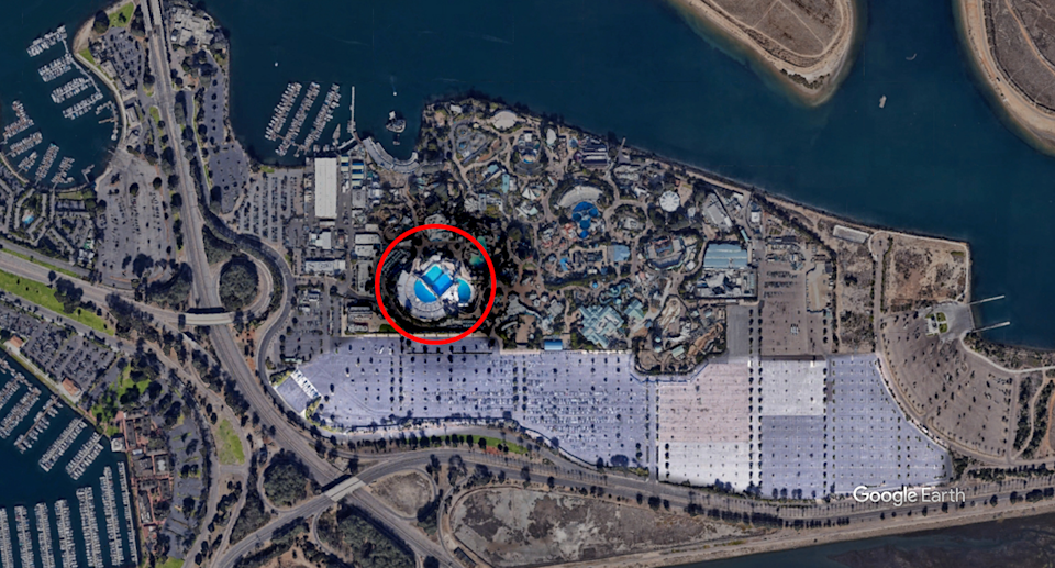 A red circle around the blue tanks where orcas live at SeaWorld Orlando compared to the carpark, highlighted in the photo, which dwarfs their home.