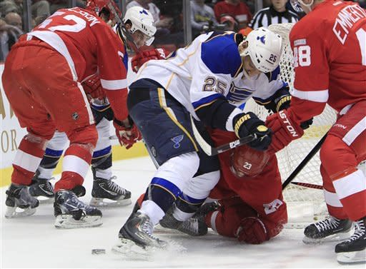 St. Louis Blues right wing Chris Stewart (25) and Detroit Red Wings defenseman Brad Stuart (23) vie for the puck during the first period of an NHL hockey game in Detroit, Monday, Jan. 23, 2012. (AP Photo/Carlos Osorio)