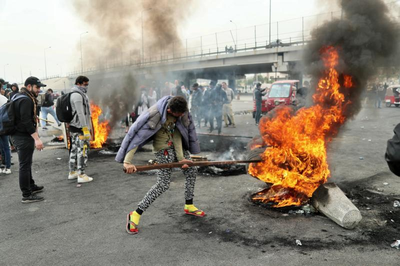 Anti-government protesters set fires and close streets during ongoing protests in downtown Baghdad, Iraq, Sunday, Jan. 19, 2020. Black smoke filled the air as protesters burned tires to block main roads in the Iraqi capital Baghdad, expressing their anger at poor services and shortages despite religious and political leaders calling for calm. (AP Photo/Hadi Mizban)
