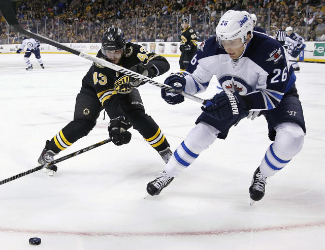 Boston Bruins' Matt Bartkowski (43) and Winnipeg Jets' Blake Wheeler (26) battle for the puck in the first period of an NHL hockey game in Boston, Saturday, Jan. 4, 2014. (AP Photo/Michael Dwyer)