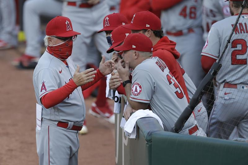 Angels manager Joe Maddon speaks with his players before a game against the Oakland Athletics.