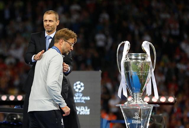 Soccer Football - Champions League Final - Real Madrid v Liverpool - NSC Olympic Stadium, Kiev, Ukraine - May 26, 2018 Liverpool manager Juergen Klopp collects his medal from UEFA President Aleksander Ceferin as he walks past the trophy after the match REUTERS/Kai Pfaffenbach