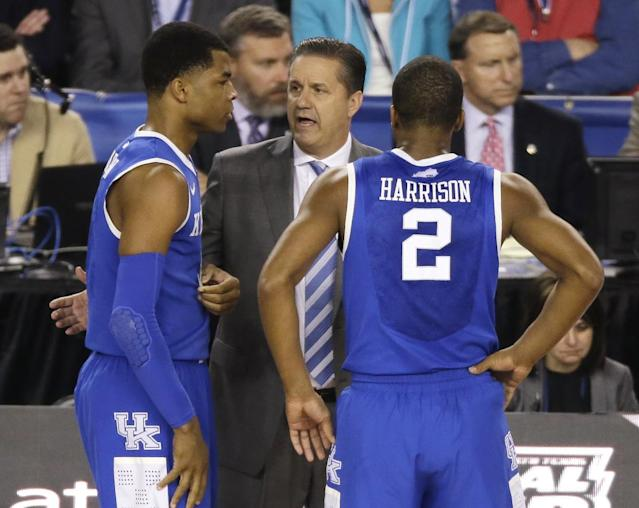 Kentucky head coach John Calipari, center, talks with guard Andrew Harrison, left, and guard Aaron Harrison during the first half of the NCAA Final Four tournament college basketball semifinal game against Wisconsin Saturday, April 5, 2014, in Arlington, Texas. (AP Photo/Tony Gutierrez)