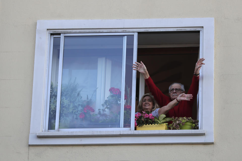 People applaud from their houses in support of the medical staff that are working on the COVID-19 virus outbreak at the Gregorio Maranon hospital in Madrid, Spain, Wednesday, April 1, 2020. The new coronavirus causes mild or moderate symptoms for most people, but for some, especially older adults and people with existing health problems, it can cause more severe illness or death. (AP Photo/Manu Fernandez)
