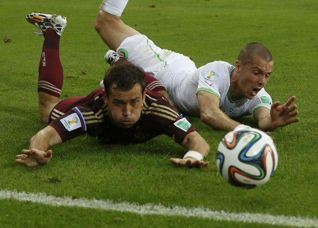 Algeria's Djamel Mesbah (R) fouls Russia's Alexander Kerzhakov during their 2014 World Cup Group H soccer match at the Baixada arena in Curitiba June 26, 2014. Mesbah received a yellow card for the foul. REUTERS/Maxim Shemetov (BRAZIL - Tags: SOCCER SPORT WORLD CUP)