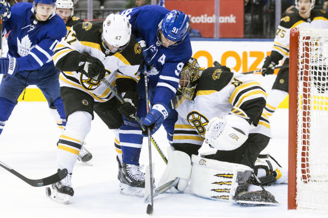 Boston Bruins' Torey Krug (47) vies for the puck with Toronto Maple Leafs' John Tavares (91) in front of Bruins goaltender Jaroslav Halak during second-period NHL hockey game action in Toronto, Monday, Nov. 26, 2018. (Chris Young/The Canadian Press via AP)