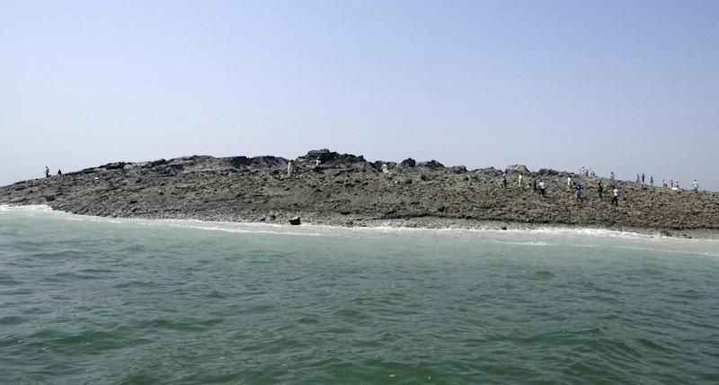 In this photo released by the Gwadar local government office on Wednesday, Sept 25, 2013, people walk on an island that reportedly emerged off the Gwadar coastline in the Arabian Sea. A deadly magnitude 7.7 earthquake struck in the remote district of Awaran in Pakistan's Baluchistan province with enough force to create a small island visible off the southern coast, Pakistani officials said. (AP Photo/Gwadar local government office)