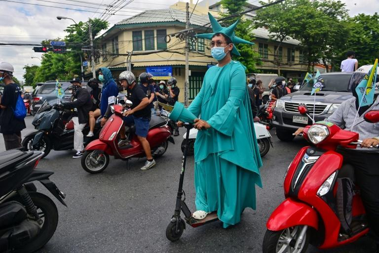 A pro-democracy protester dressed as the Statue of Liberty rides an electric scooter during the anti-government demonstration in Bangkok