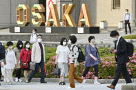 People wearing face masks walk by the city hall in Osaka, western Japan, May 14, 2021. Hospitals in Osaka, Japan's third-biggest city and only 2 1/2 hours by bullet train from Summer Olympics host Tokyo, are overflowing with coronavirus patients. About 35,000 people nationwide - twice the number of those in hospitals - must stay at home with the disease, often becoming seriously ill and sometimes dying before they can get medical care. (Kyodo News via AP)
