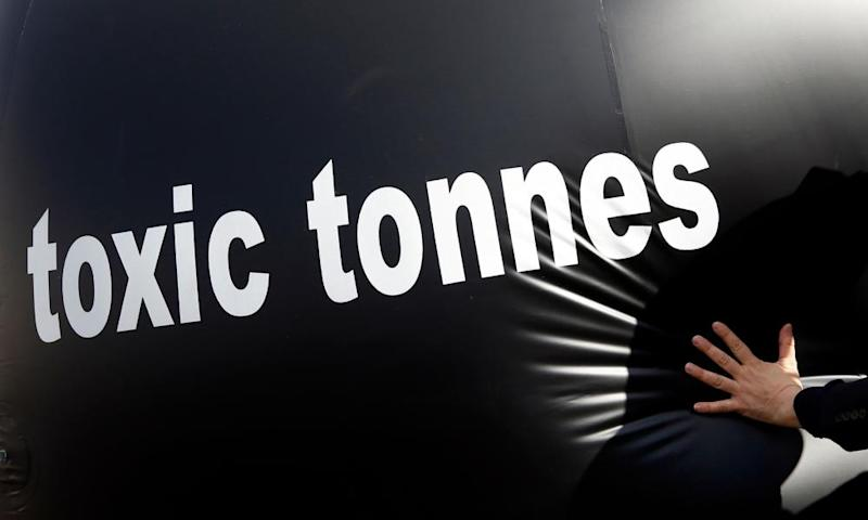 """An environmental activist pushes a giant ball with the words, """"toxic tonnes"""" during a protest over carbon pricing reforms outside the European Parliament in Brussels"""