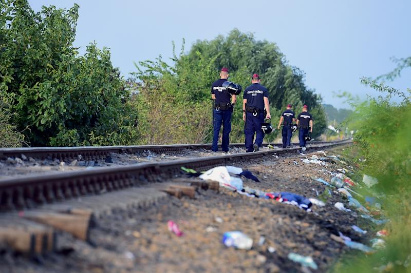 Hungarian police officers walk on the train tracks at the Hungarian-Serbian border, near the village of Roszke, on September 14, 2015 (AFP Photo/Attila Kisbenedek)