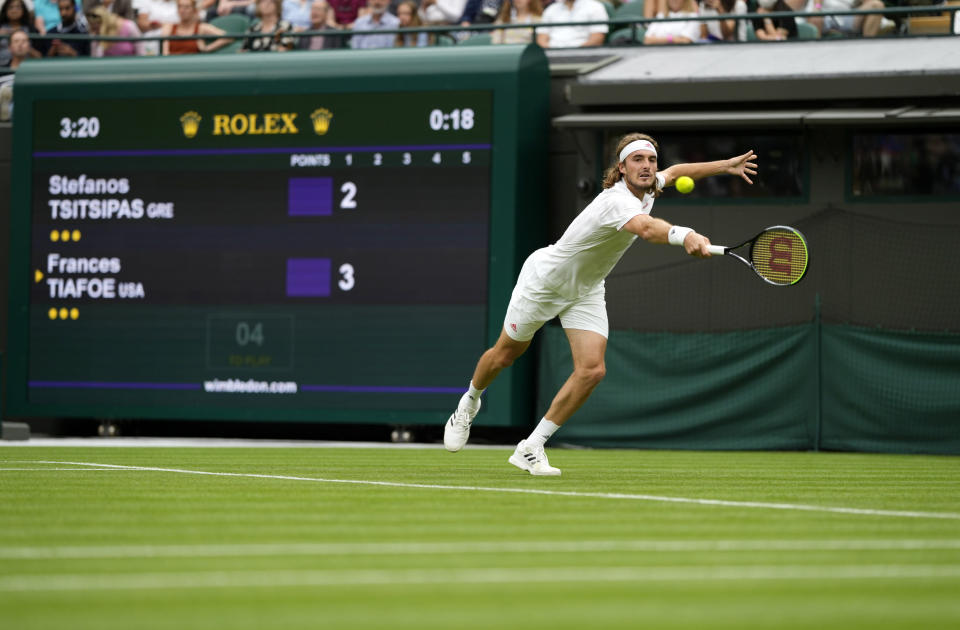 Stefanos Tsitsipas of Greece returns the ball to Frances Tiafoe of the US during the men's singles match on day one of the Wimbledon Tennis Championships in London, Monday June 28, 2021. (AP Photo/Alastair Grant)