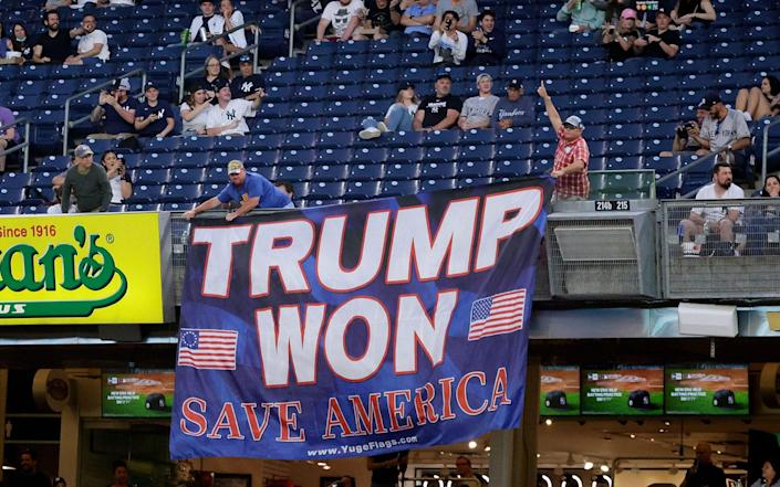 Two supporters of former US President Donald Trump display a banner - JASON SZENES/Shutterstock