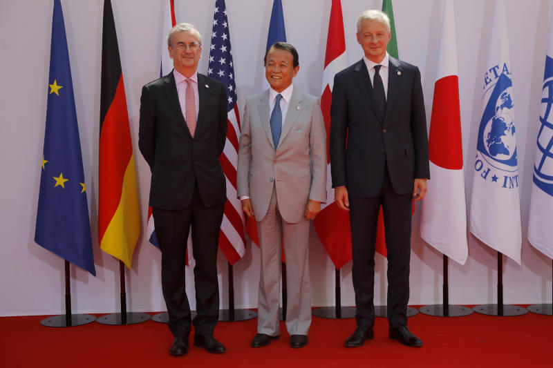French Finance Minister Bruno Le Maire, right, welcomes Japan's Finance Minister Taro Aso , center, with Governor of the Bank of France Francois Villeroy de Galhau, at the G-7 Finance Wednesday July 17, 2019.The top finance officials of the Group of Seven rich democracies are arriving at Chantilly, at the start of a two-day meeting aimed at finding common ground on how to tax technology companies and on the risk from new digital currencies. (AP Photo/Michel Euler)