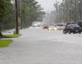 Cars sit stalled on a flooded McNeese Street during heavy rains in Lake Charles, La., Monday, May 17, 2021. (Rick Hickman/American Press via AP)