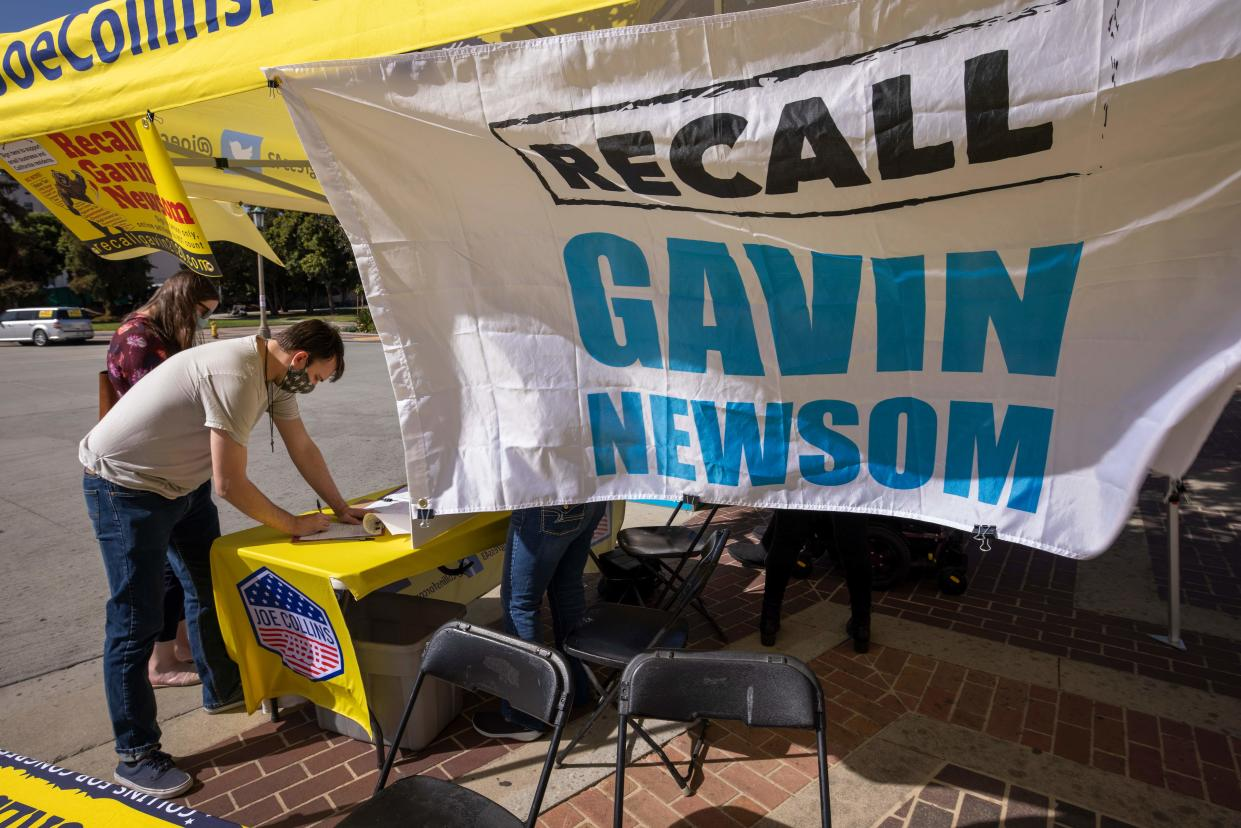 A man signs a petition as conservative activists gather signatures in a recall effort against California Governor Gavin Newsom near Pasadena City Hall, in Pasadena, California on February 28, 2021. (David Mcnew/AFP via Getty Images)