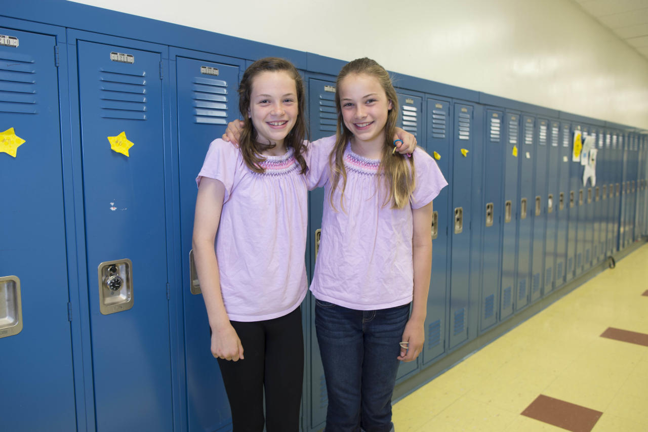 In this Thursday, June 6, 2013 photo, Emma Merk, left, and her twin sister, Katie, one of the twenty-four sets of twins from Highcrest Middle School in Wilmette, Ill. pose for a portrait art the school. The group is attempting to break a Guinness World record for the amount of twins in one grade which is currently sixteen sets. (AP Photo/Scott Eisen)